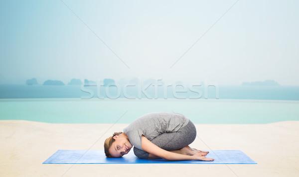 happy woman making yoga in child pose on mat Stock photo © dolgachov