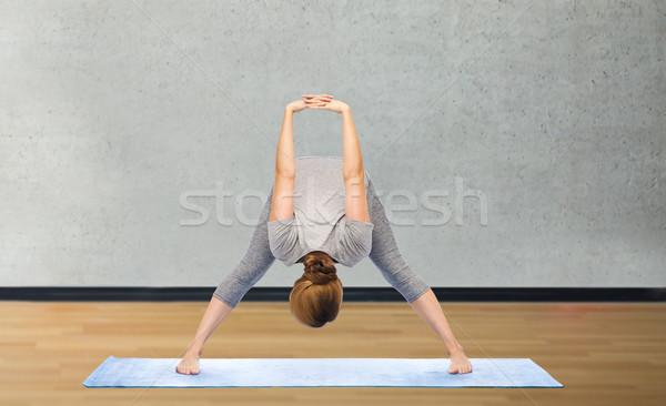 woman making yoga in wide-legged forward bend pose Stock photo © dolgachov