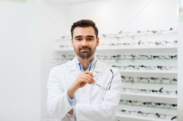 man optician with glasses in coat at optics store Stock photo © dolgachov