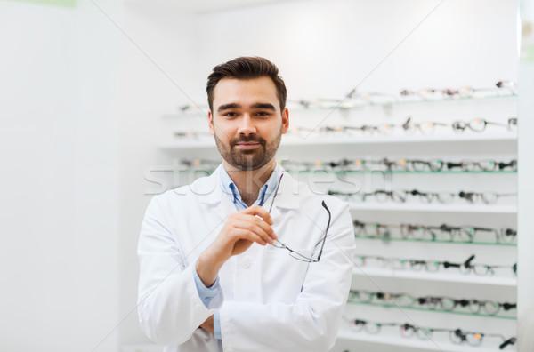 Człowiek optyk okulary płaszcz optyka sklepu Zdjęcia stock © dolgachov