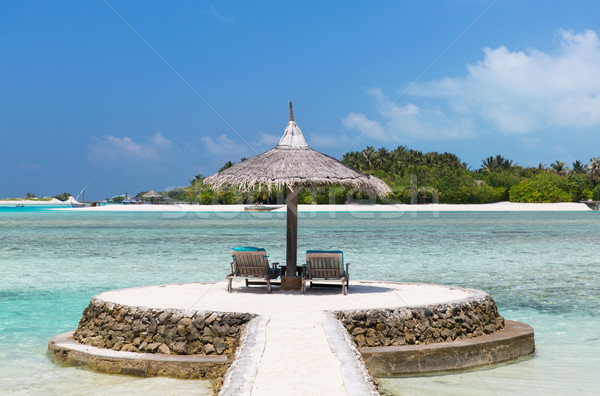 palapa and sunbeds by sea on maldives beach Stock photo © dolgachov