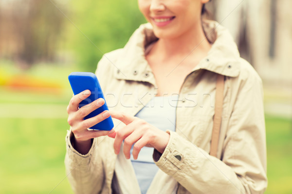 close up of woman calling on smartphone in park Stock photo © dolgachov