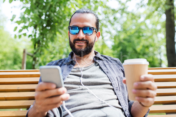 man with earphones and smartphone drinking coffee Stock photo © dolgachov