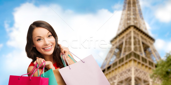 Stock photo: happy woman with shopping bags over eiffel tower