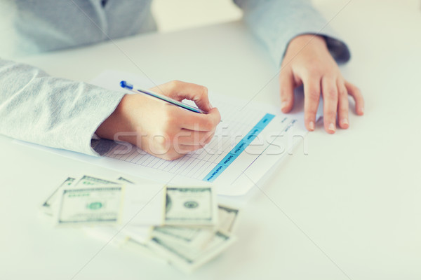 Stock photo: close up of hands with money filling tax form