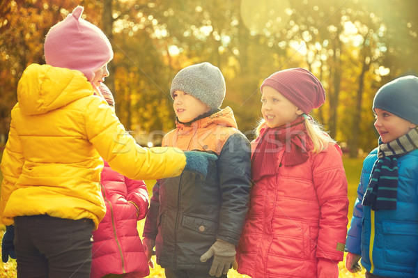 kids in autumn park counting and choosing leader Stock photo © dolgachov