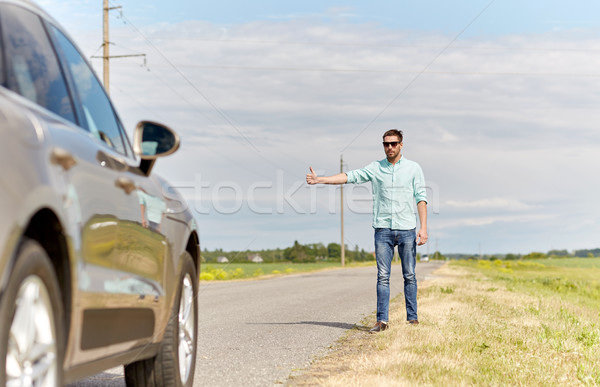 man hitchhiking and stopping car at countryside Stock photo © dolgachov