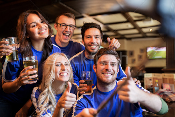 football fans with beer taking selfie at pub Stock photo © dolgachov
