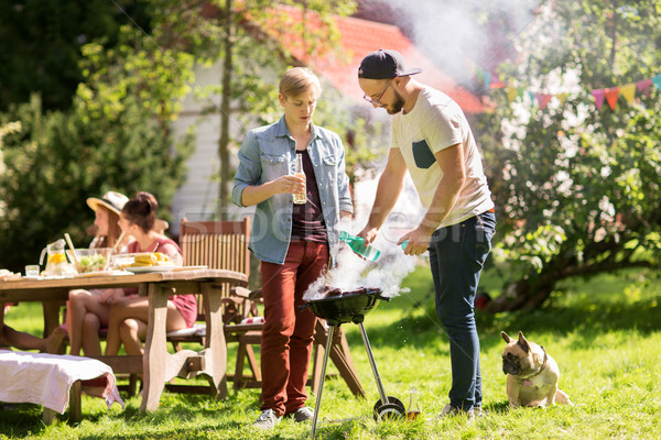 friends making barbecue grill at summer party Stock photo © dolgachov