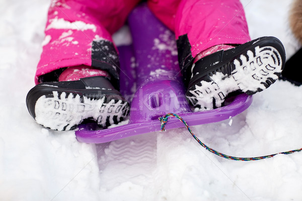 close up of kids feet in winter boots on sled Stock photo © dolgachov