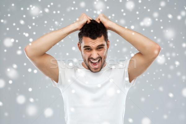 crazy shouting man in t-shirt over snow background Stock photo © dolgachov