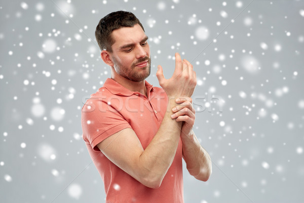 unhappy man suffering from pain in hand over snow Stock photo © dolgachov