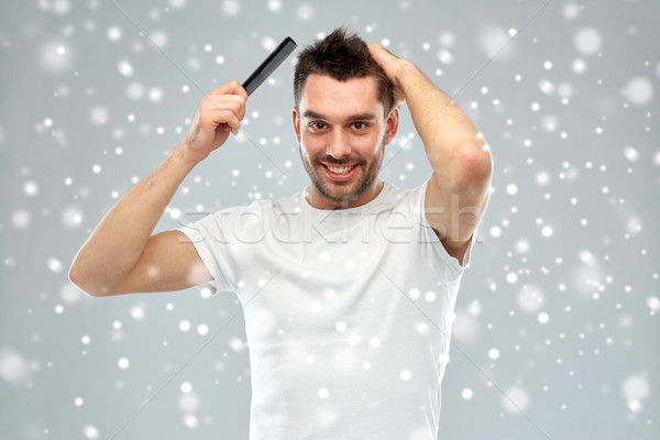 happy man brushing hair with comb over snow Stock photo © dolgachov