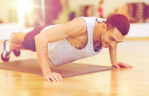 smiling man doing push-ups in the gym Stock photo © dolgachov