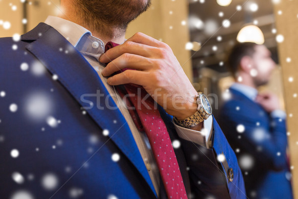 close up of man trying tie on at clothing store Stock photo © dolgachov
