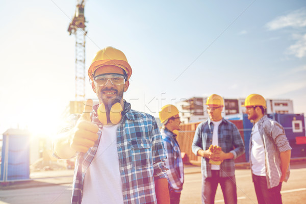 builders showing thumbs up at construction site Stock photo © dolgachov