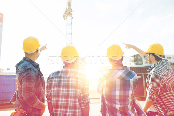 group of builders in hardhats at construction site Stock photo © dolgachov