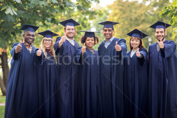 happy students or bachelors showing thumbs up Stock photo © dolgachov