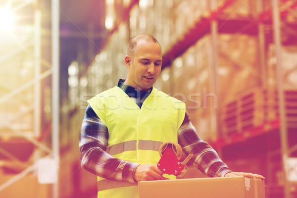 man in safety vest packing box at warehouse Stock photo © dolgachov
