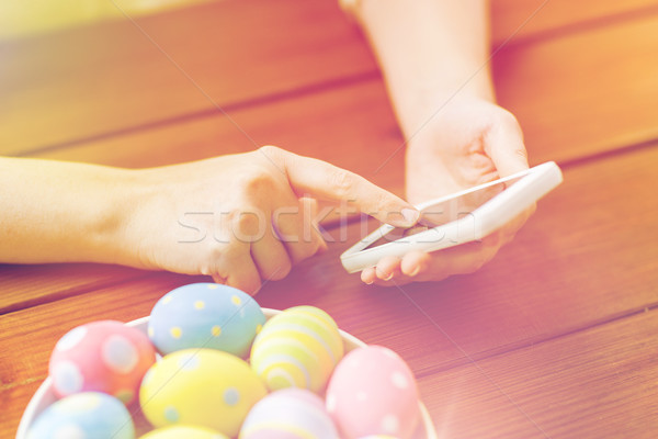 close up of hands with easter eggs and smartphone Stock photo © dolgachov