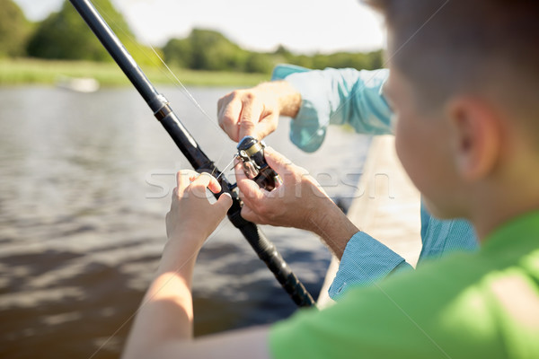 boy and grandfather with fishing rod on river Stock photo © dolgachov