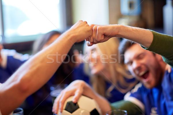 soccer fans with ball celebrating victory at bar Stock photo © dolgachov
