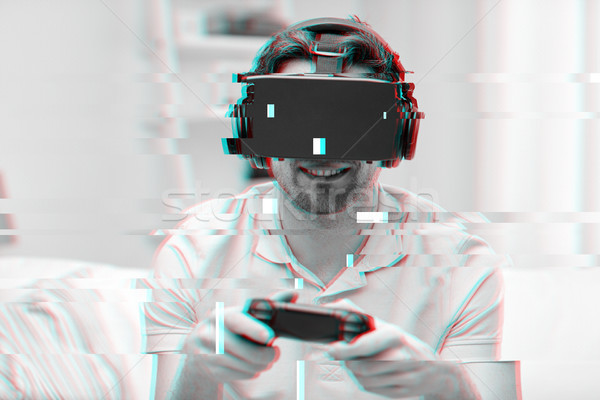 man in virtual reality headset with controller Stock photo © dolgachov