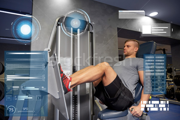 man flexing leg muscles on gym machine Stock photo © dolgachov