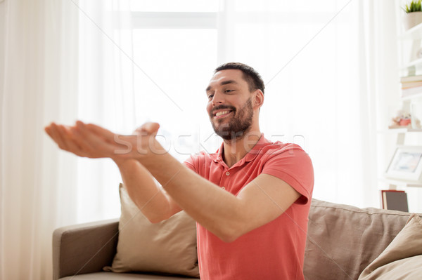 Stock photo: happy man holding something imaginary at home
