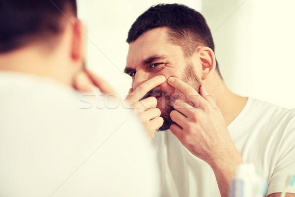 man squeezing pimple at bathroom mirror Stock photo © dolgachov