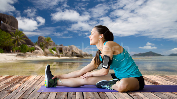 woman with smartphone stretching leg on mat Stock photo © dolgachov
