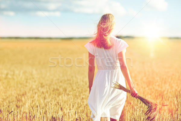 young woman with cereal spikelets walking on field Stock photo © dolgachov