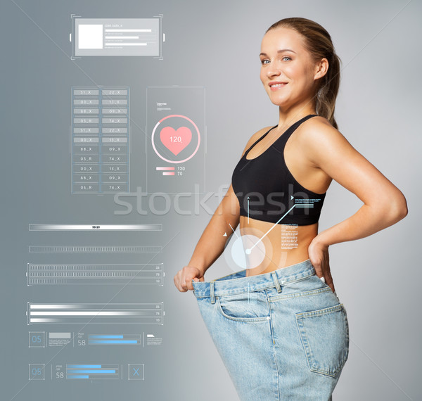 Stock photo: young slim sporty woman in large size pants