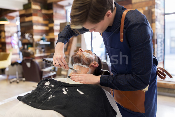 barber with straight razor shaving clients beard Stock photo © dolgachov