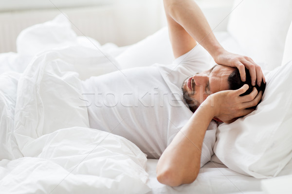 man in bed at home suffering from headache Stock photo © dolgachov