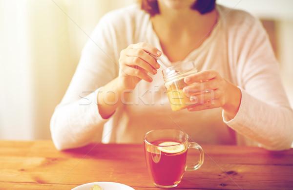 close up of ill woman drinking tea with honey Stock photo © dolgachov