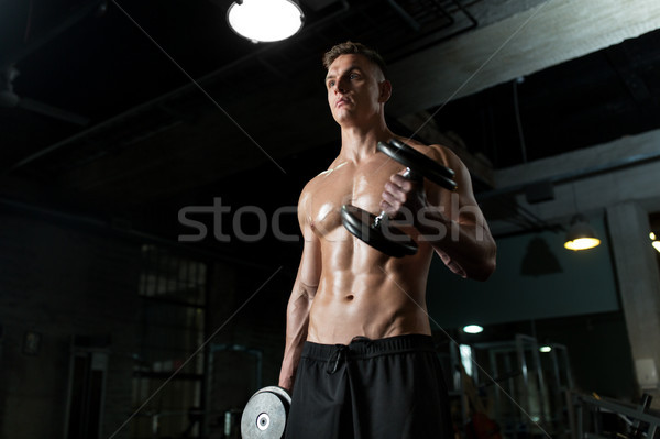 close up of man with dumbbells exercising in gym Stock photo © dolgachov
