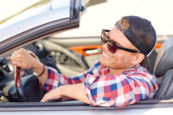 happy young man in shades driving convertible car Stock photo © dolgachov