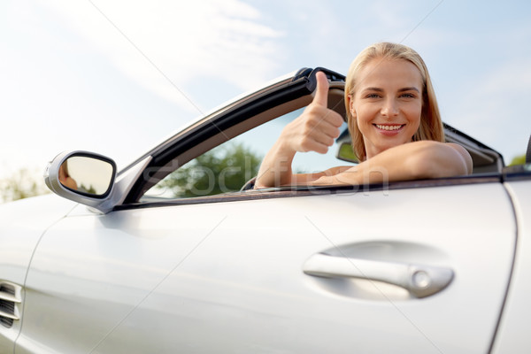 happy young woman in convertible car thumbs up Stock photo © dolgachov