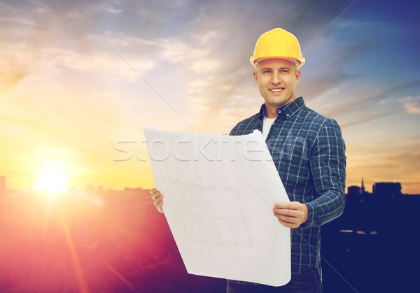 male builder in yellow hard hat with blueprint Stock photo © dolgachov