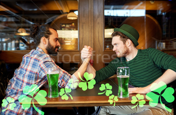 men drinking green beer and arm wrestling at pub Stock photo © dolgachov