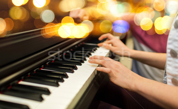 close up of woman hands playing piano over lights Stock photo © dolgachov