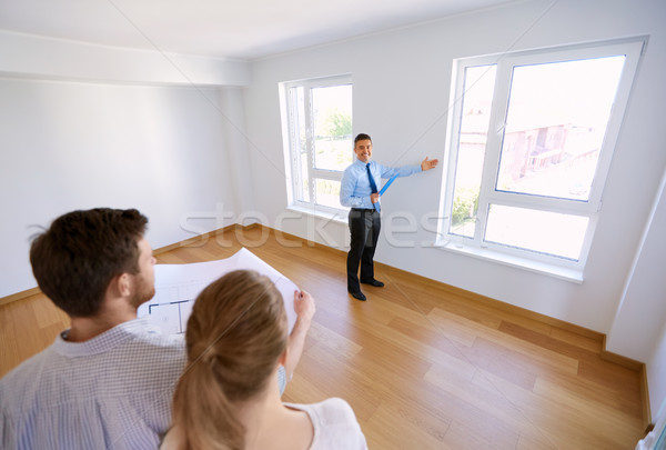 realtor showing new home to couple with blueprint Stock photo © dolgachov