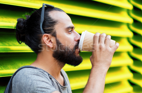 man drinking coffee from paper cup over wall Stock photo © dolgachov