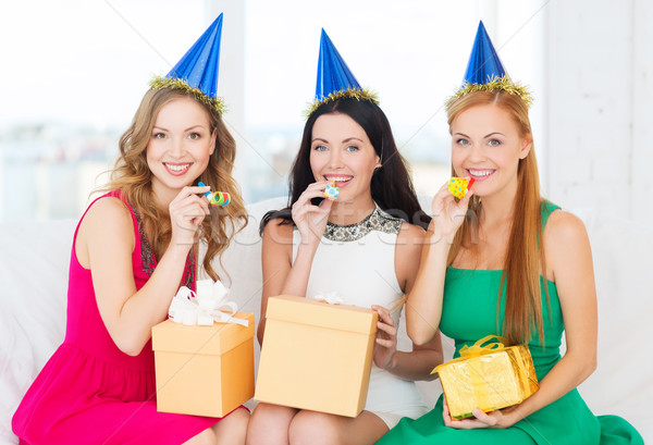 three women wearing hats with gifts blowing horns Stock photo © dolgachov