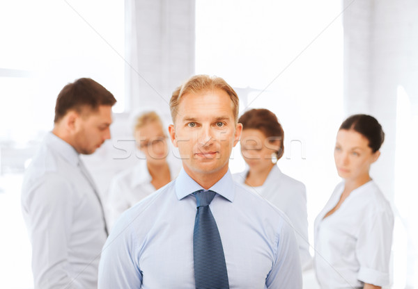 businessman in office with group on the back Stock photo © dolgachov