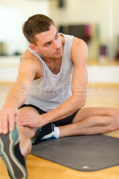 serious man stretching on mat in the gym Stock photo © dolgachov