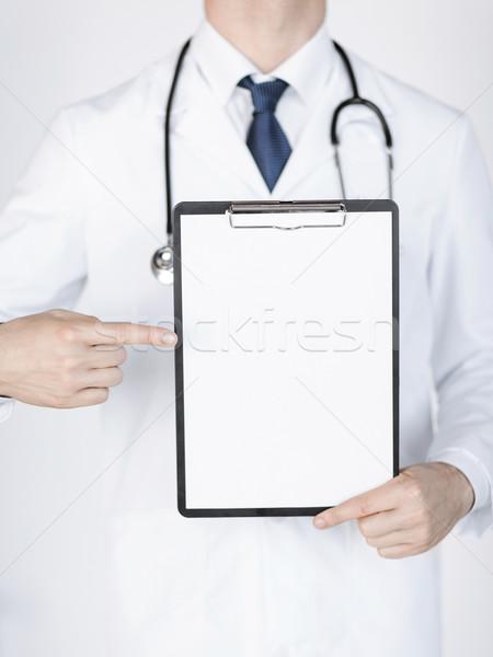 Médico senalando blanco papel familia Foto stock © dolgachov