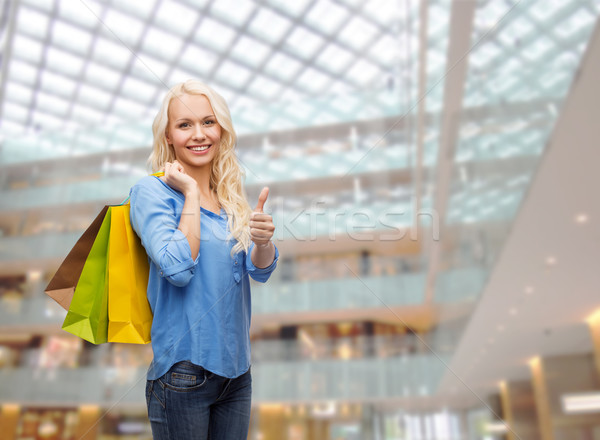 smiling woman with shopping bags showing thumbs up Stock photo © dolgachov