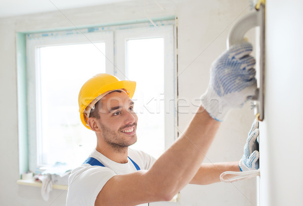 smiling builder working with grinding tool indoors Stock photo © dolgachov